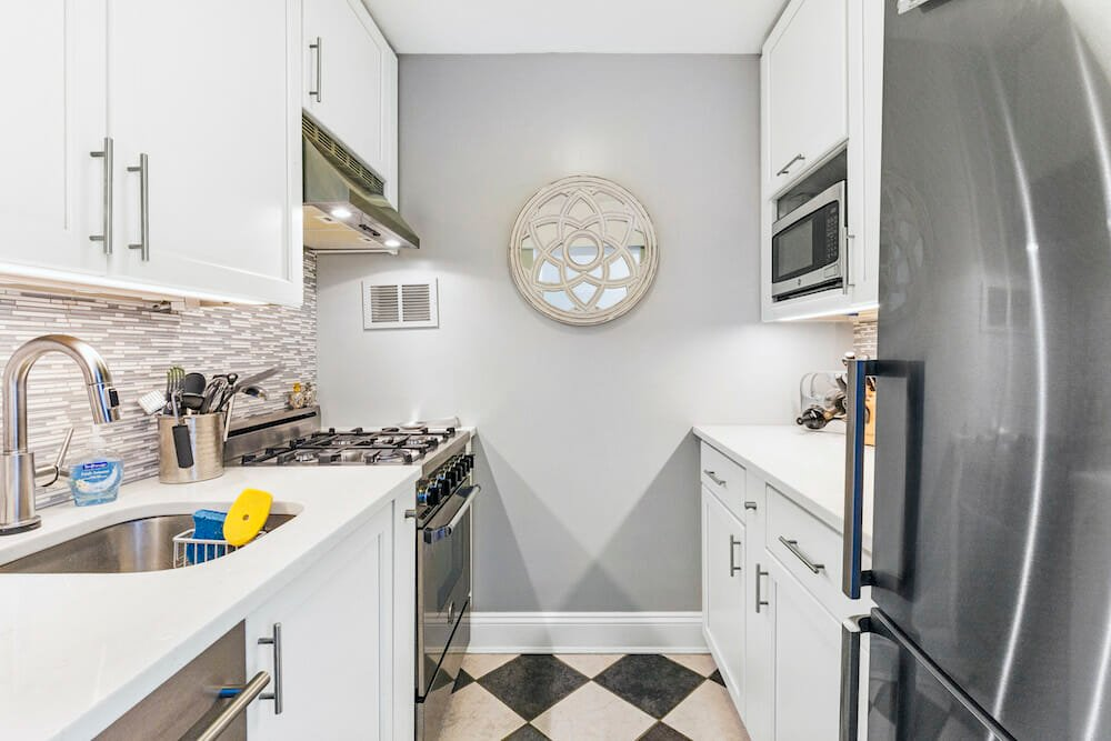 small galley kitchen with white cabinets