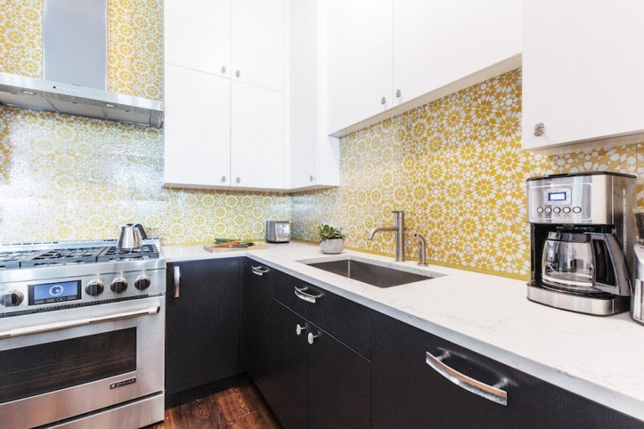 Kitchen counter with white cabinets and yellow kitchen tile backsplash