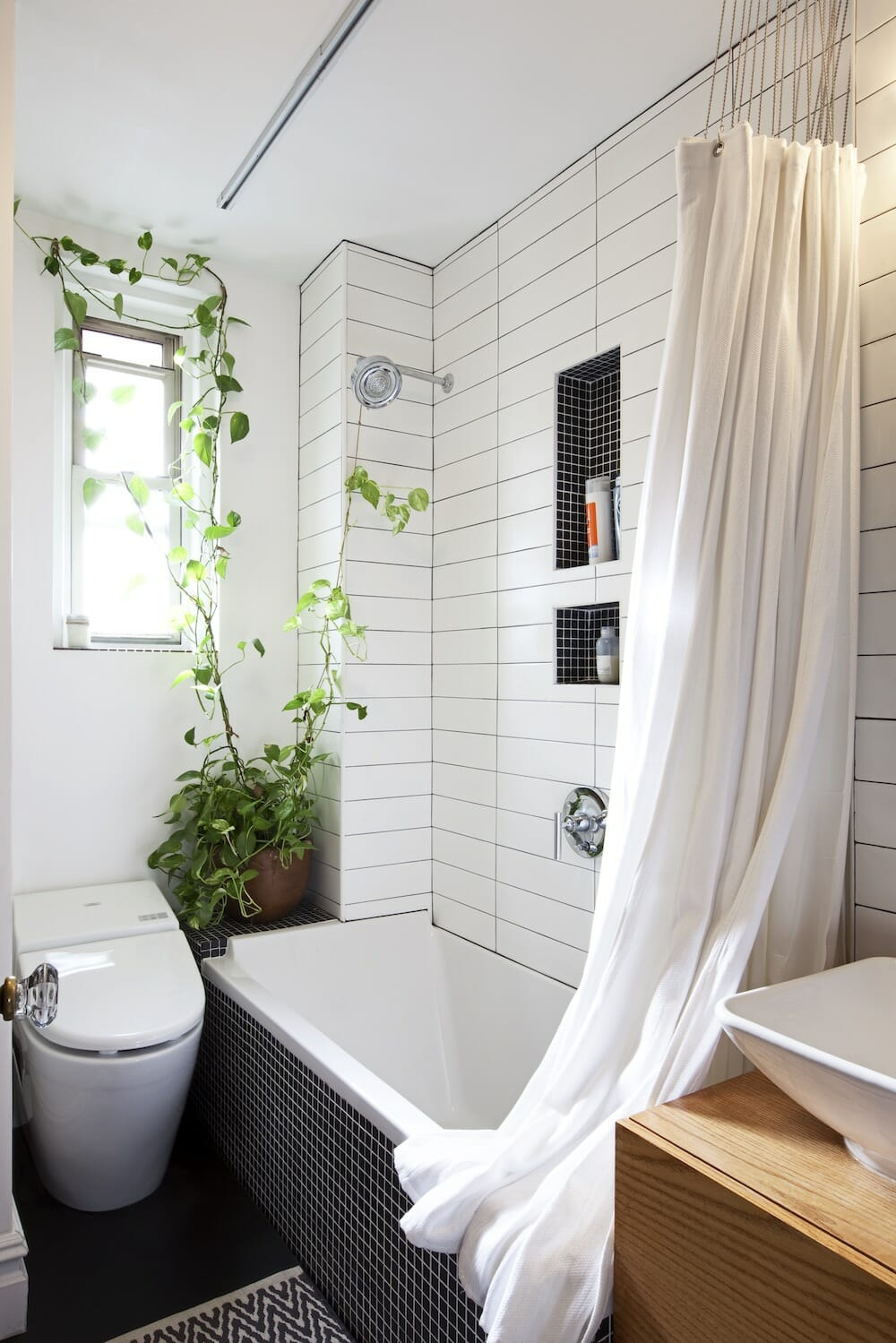 This black and white bathroom features The shower-bath wall features long white tiles offset with a darker grout