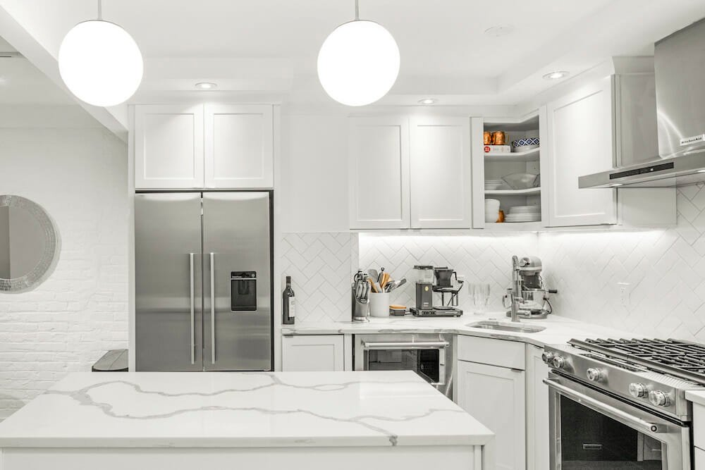 Kitchen with white Shaker-style cabinets, white quartz countertops and metal refrigerator and stove