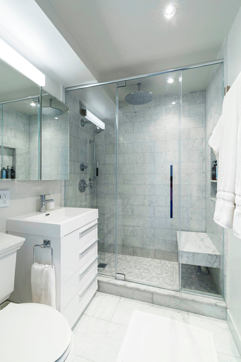 Replacing the bathtub with a glass shower opens the space and is more practical for homeowners
