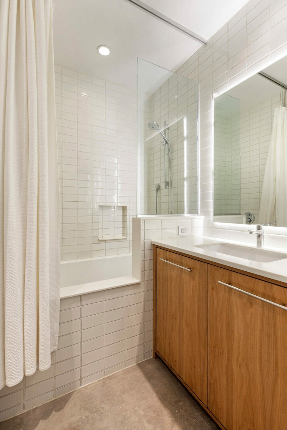 Bathroom with a white subway tile soaking tub and poured concrete floor