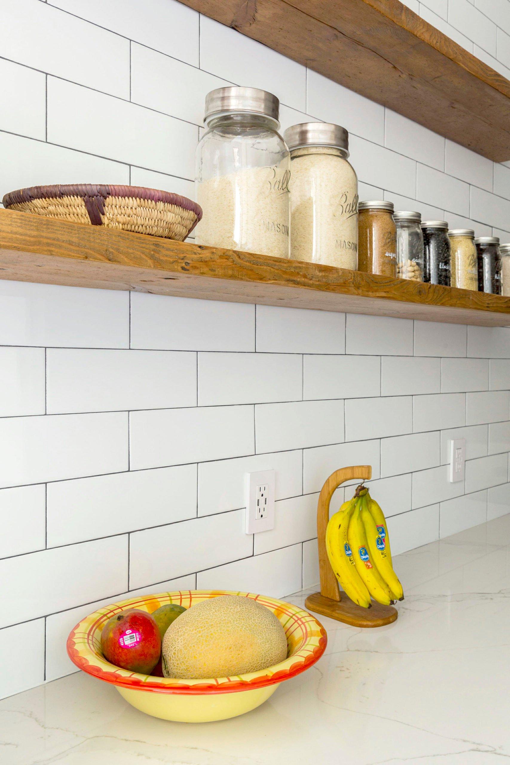 Imagen de una encimera de cocina con un metro blanco hecho de baldosas de metro y estantes abiertos
