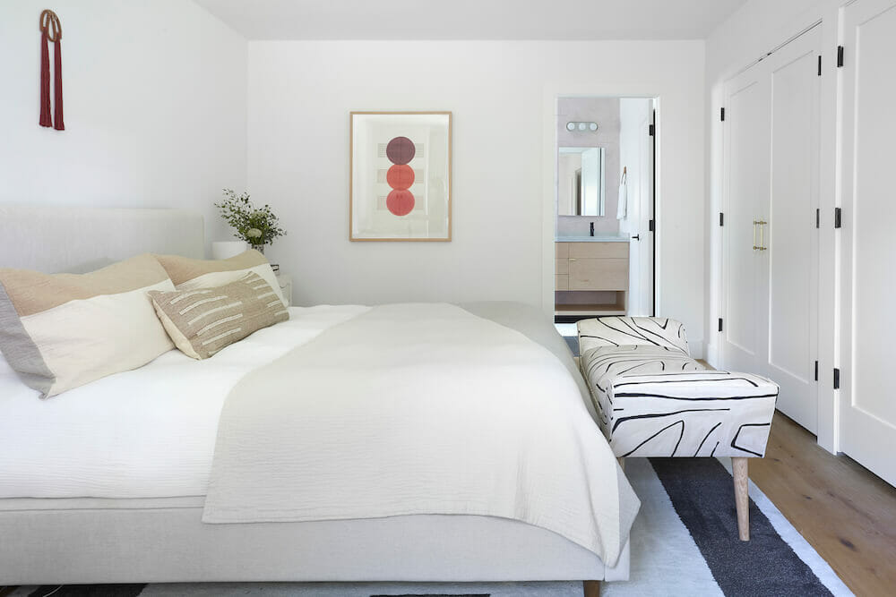 master bedroom with lounging bench at the foot of bed