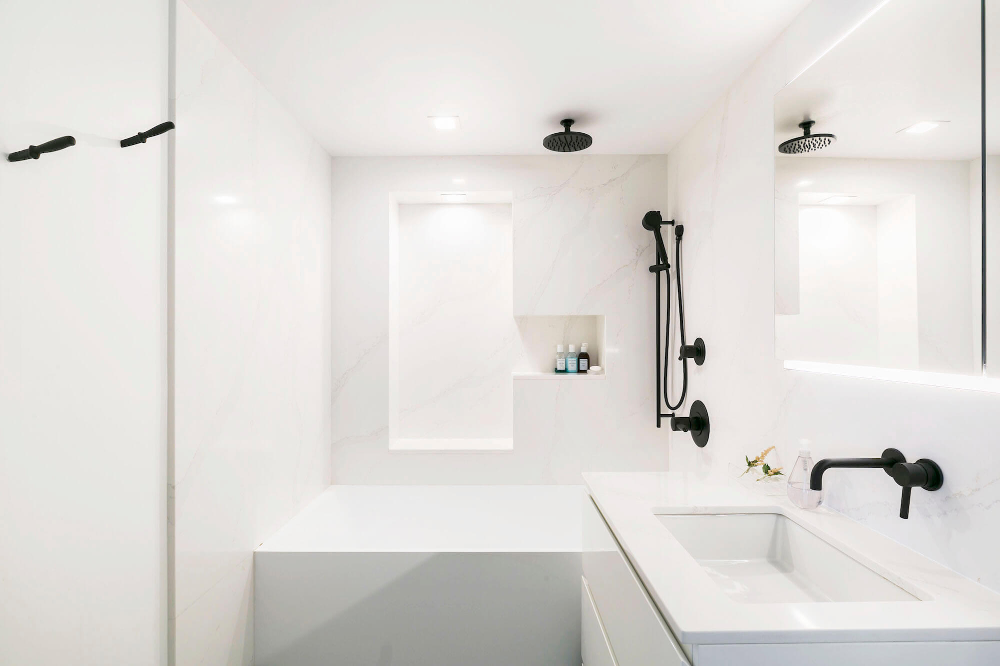 A modern loft bathroom with white marble and black fixtures