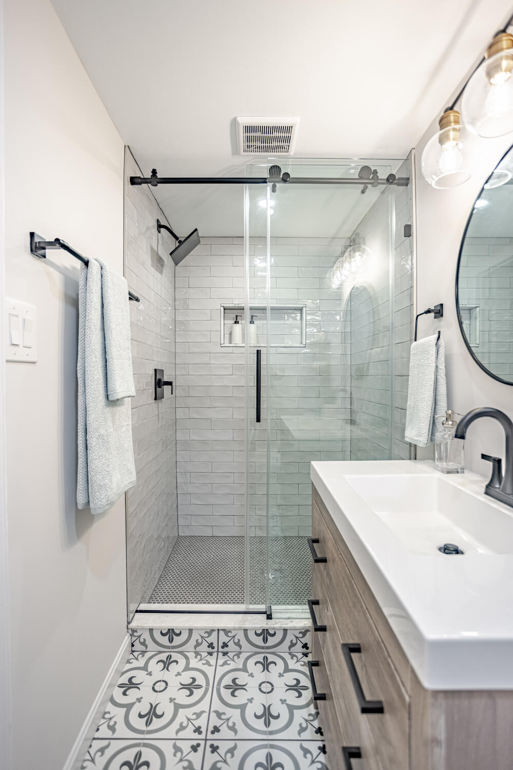 A modern bathroom design of Moroccan tile floor and subway tile shower