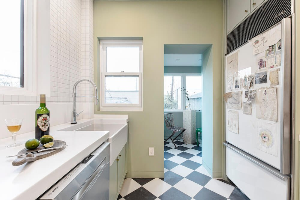 Image of a newly renovated kitchen with green walls and farmhouse sink