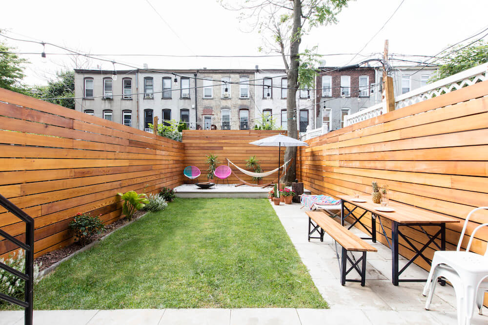 Image of a remodeled backyard with high wooden walls, fresh sod and lounge area