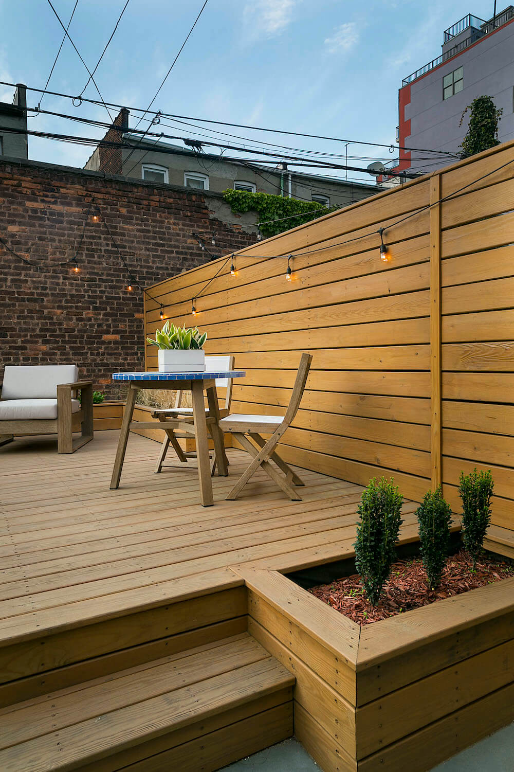 Image of a renovated backyard with wooden walls and built-in planters