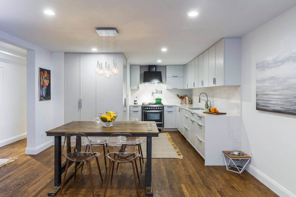 Image of a renovated kitchen with white kitchen cabinets and dining area