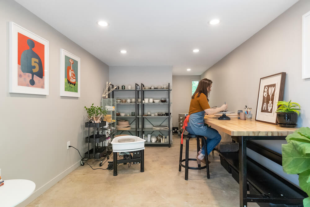 Grey Ceramic Art Studio with poured concrete flooring, wooden work bench and a minimal black storage, view from entrance