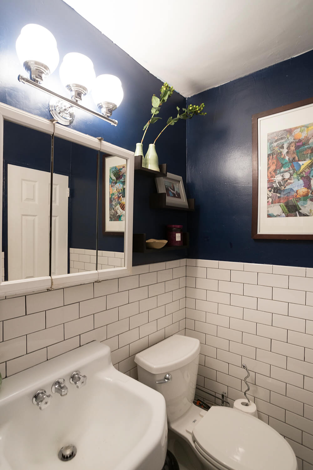 A modern bathroom design of blue walls and white subway tile