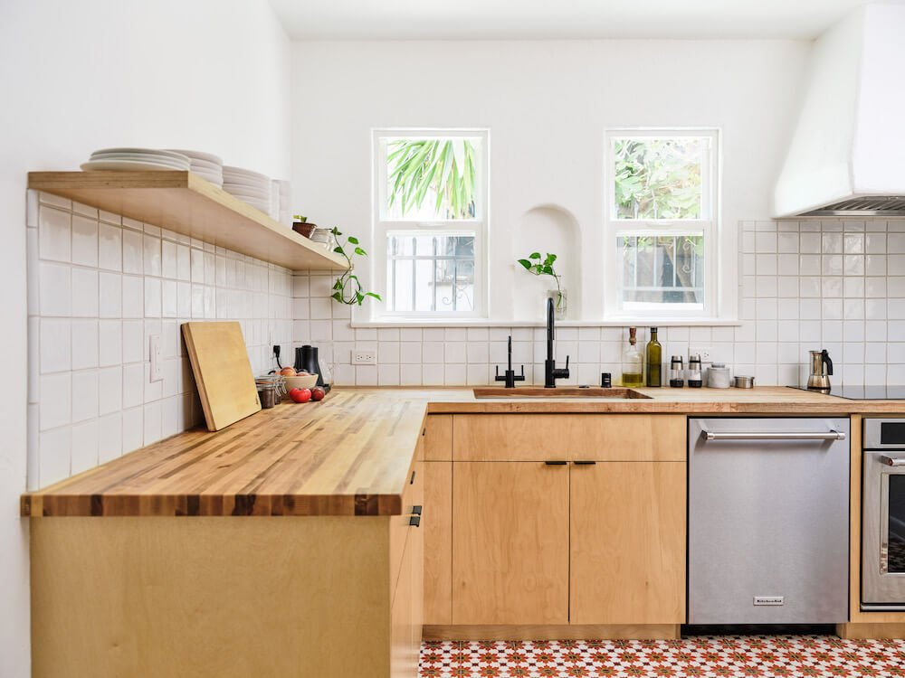 Natural wood and white kitchen with open shelf and undermount sink after renovation