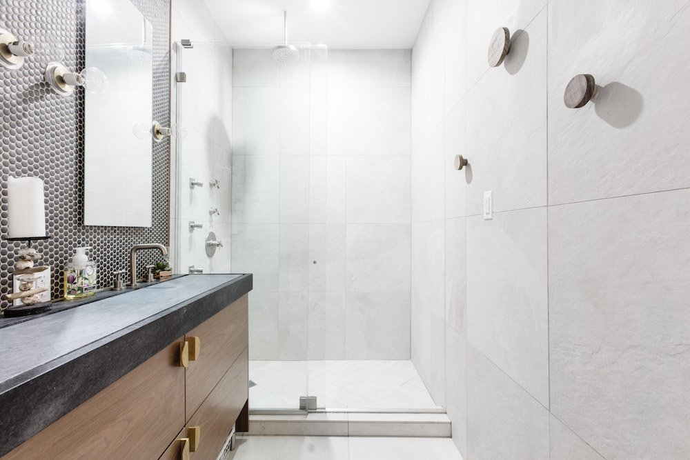 Small white bathroom with glass separator and sink vanity after renovation